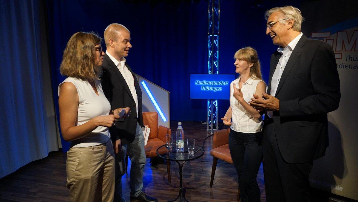 Staatssekretär Malte Krückels im GEspräch mit drei weiteren Personen. Im Hintergrund eine Interviewumgebung.