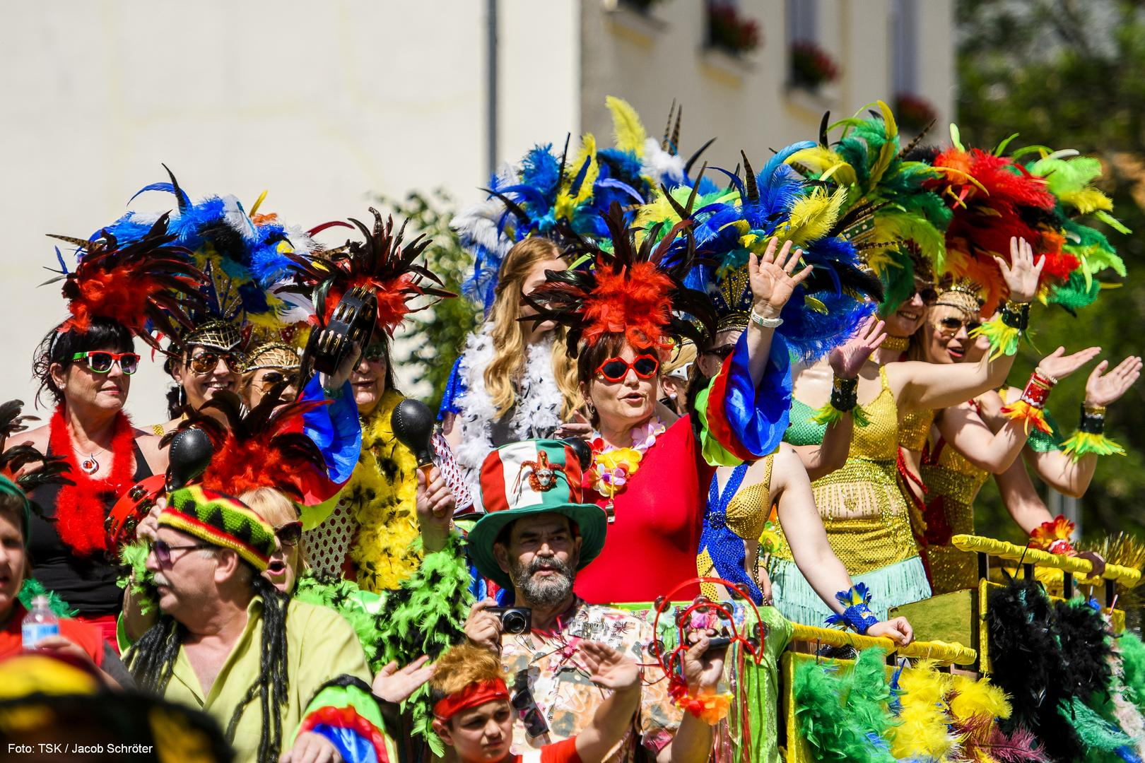 Eine Gruppe von farbenfroh gekleideteten Menschen die von einer Tribüne nach unten winken.