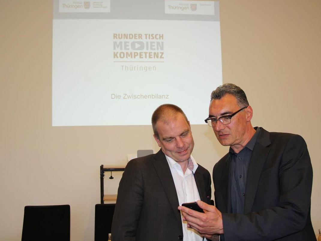 Staatssekretär Malte Krückels lässt sich auf einem Smartphone etwas zeigen. Im Hintergrund die Präsentation des Runden Tischs Medienstandort.