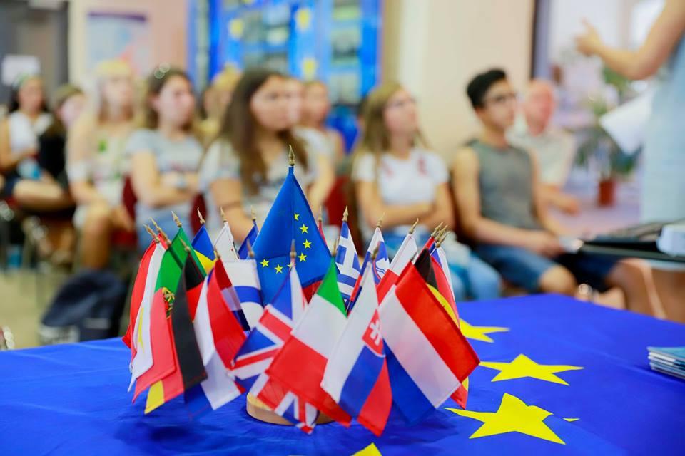 Eine Menangerie von kleienen Flaggen aus europäischen Ländern auf der EU Flagge. Im Hintergrund eine Gruppe von Frauen die zuhören.